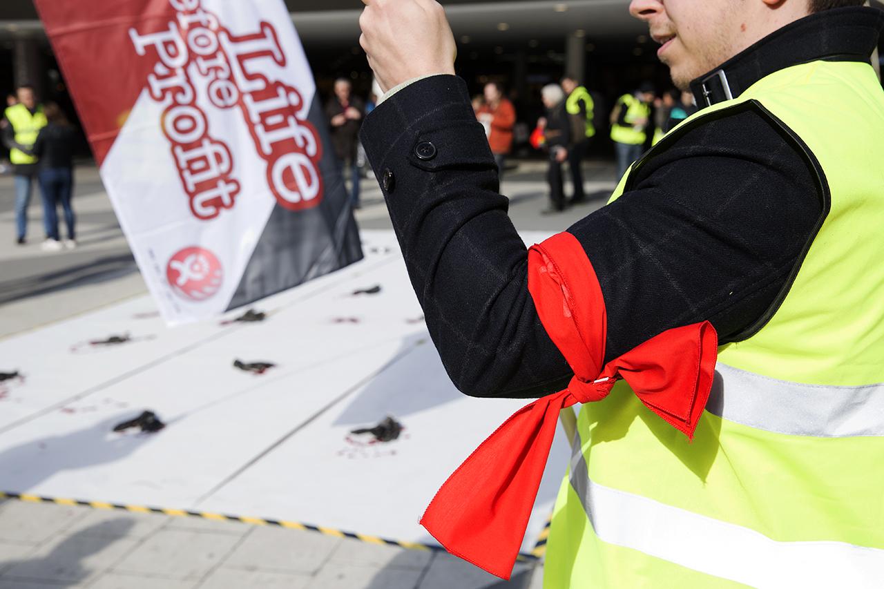 Röd armbindel vid manifestation om säkrare arbetsplatser.